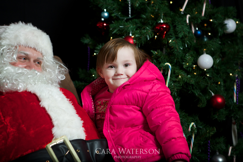 girl in pink coat on santas lap