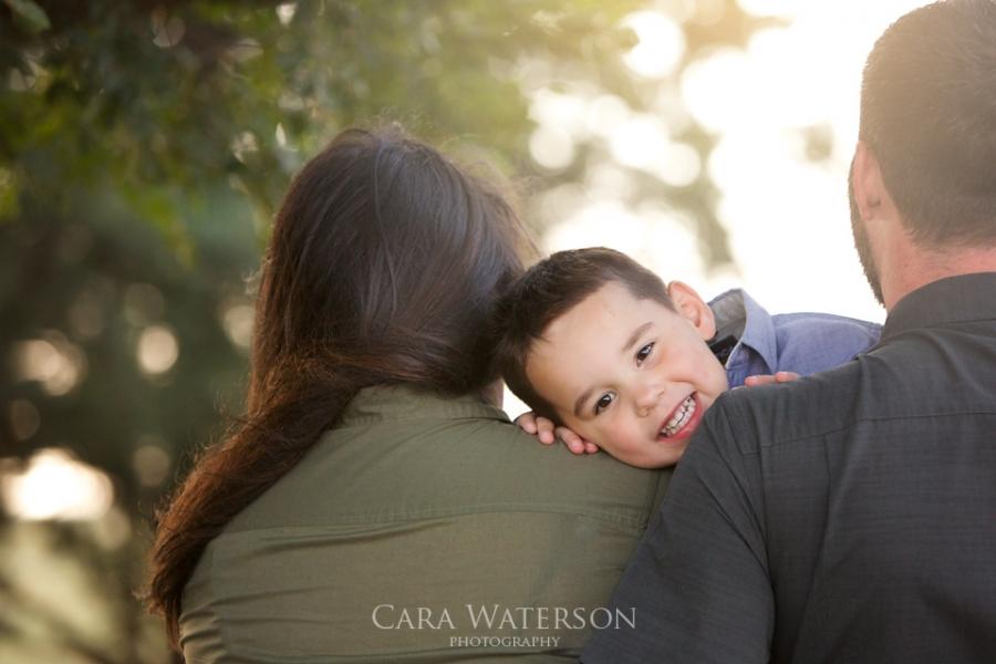 boys face over parents shoulders